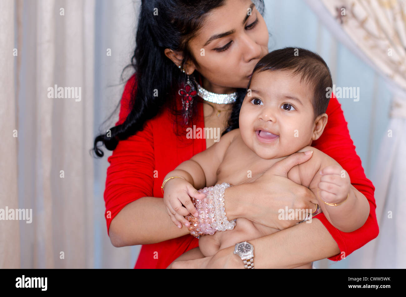 Indian mother kissing son bébé, piscine intérieure Photo Stock