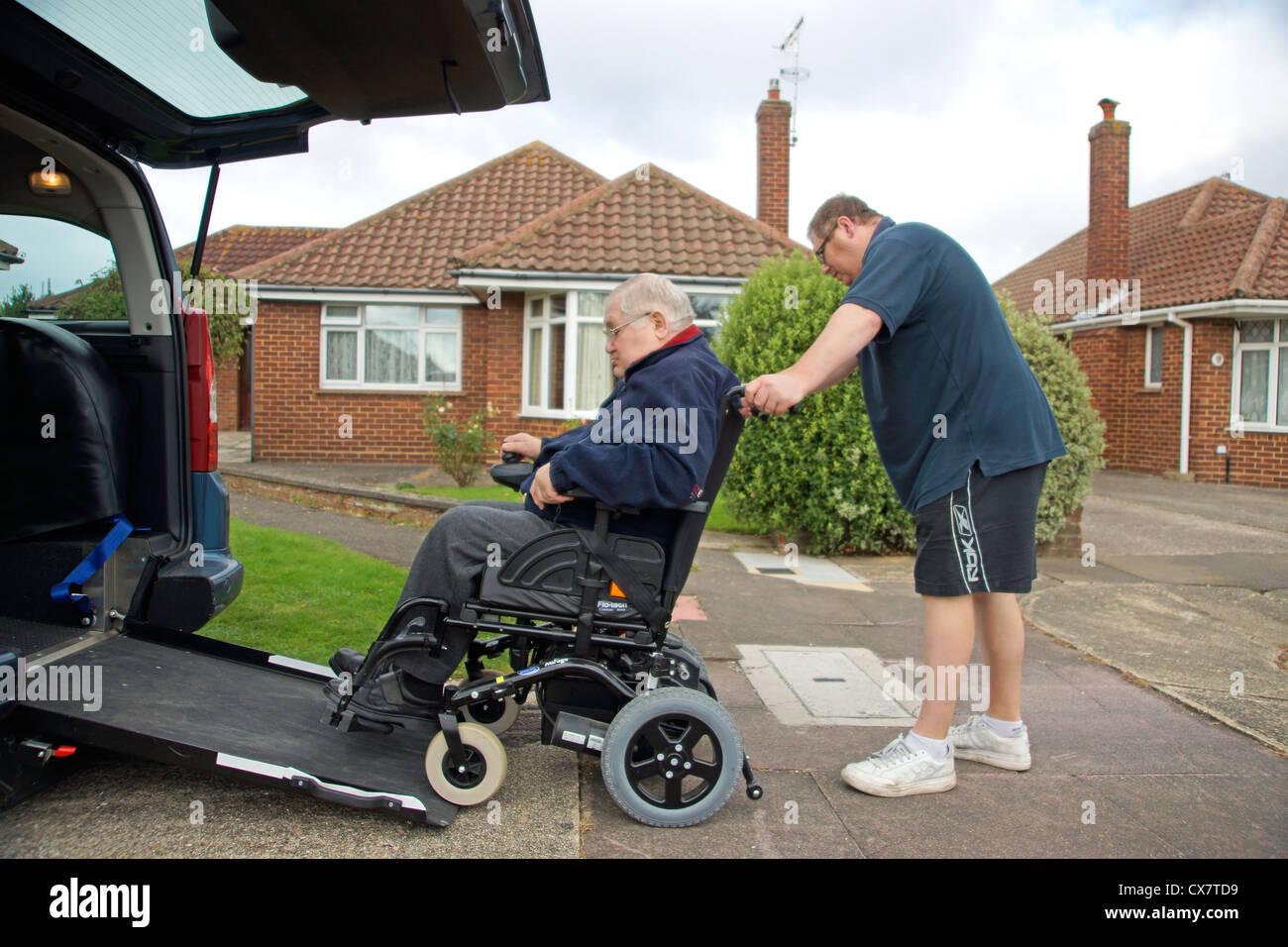 Carer mâle fils de pousser un vieil homme handicapé dans un fauteuil roulant sur un bâti en rampe Photo Stock