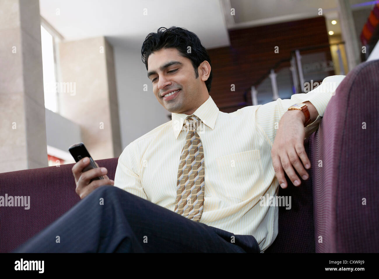 Businessman using cell phone on sofa Photo Stock