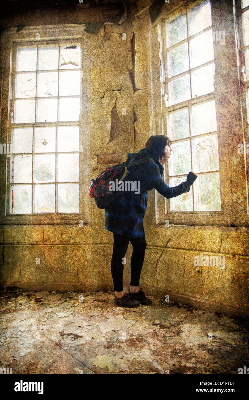 Peur à la femme par la fenêtre Photo Stock