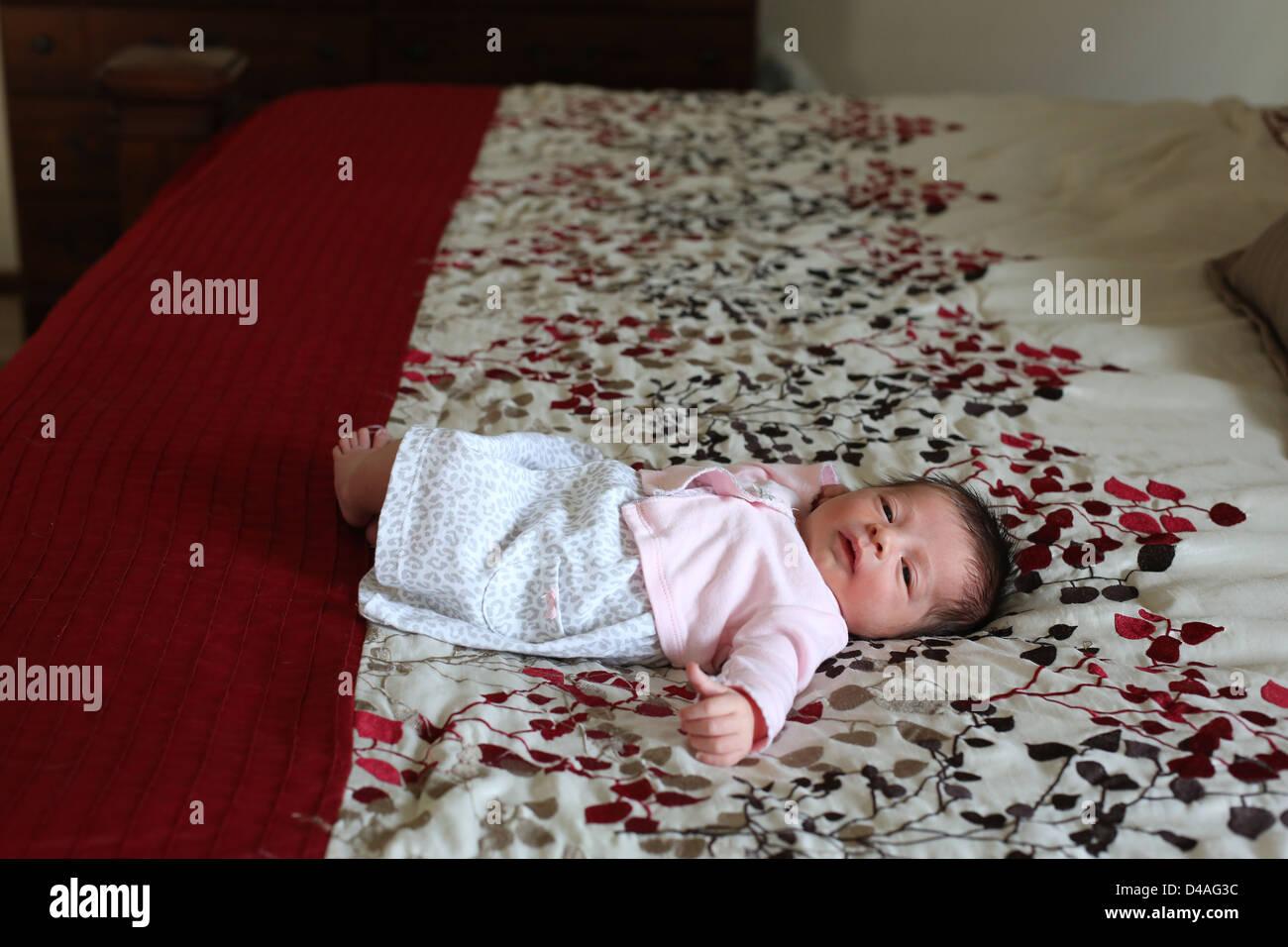Un tout petit bébé nouveau-né allongé sur un grand lit. Photo Stock