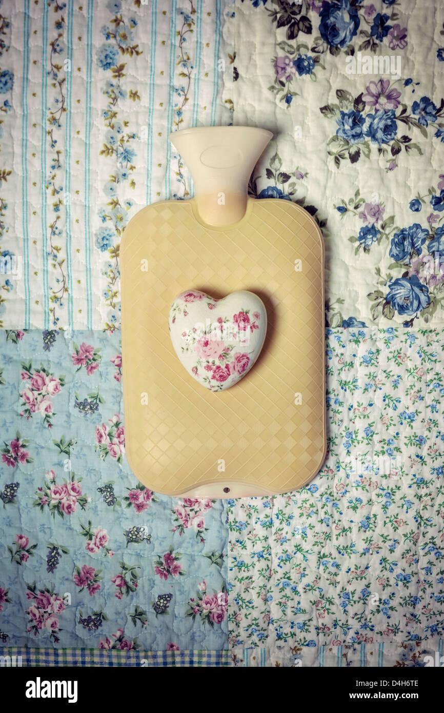 Une bouteille d'eau chaude sur un lit d'époque avec un cœur floral Photo Stock