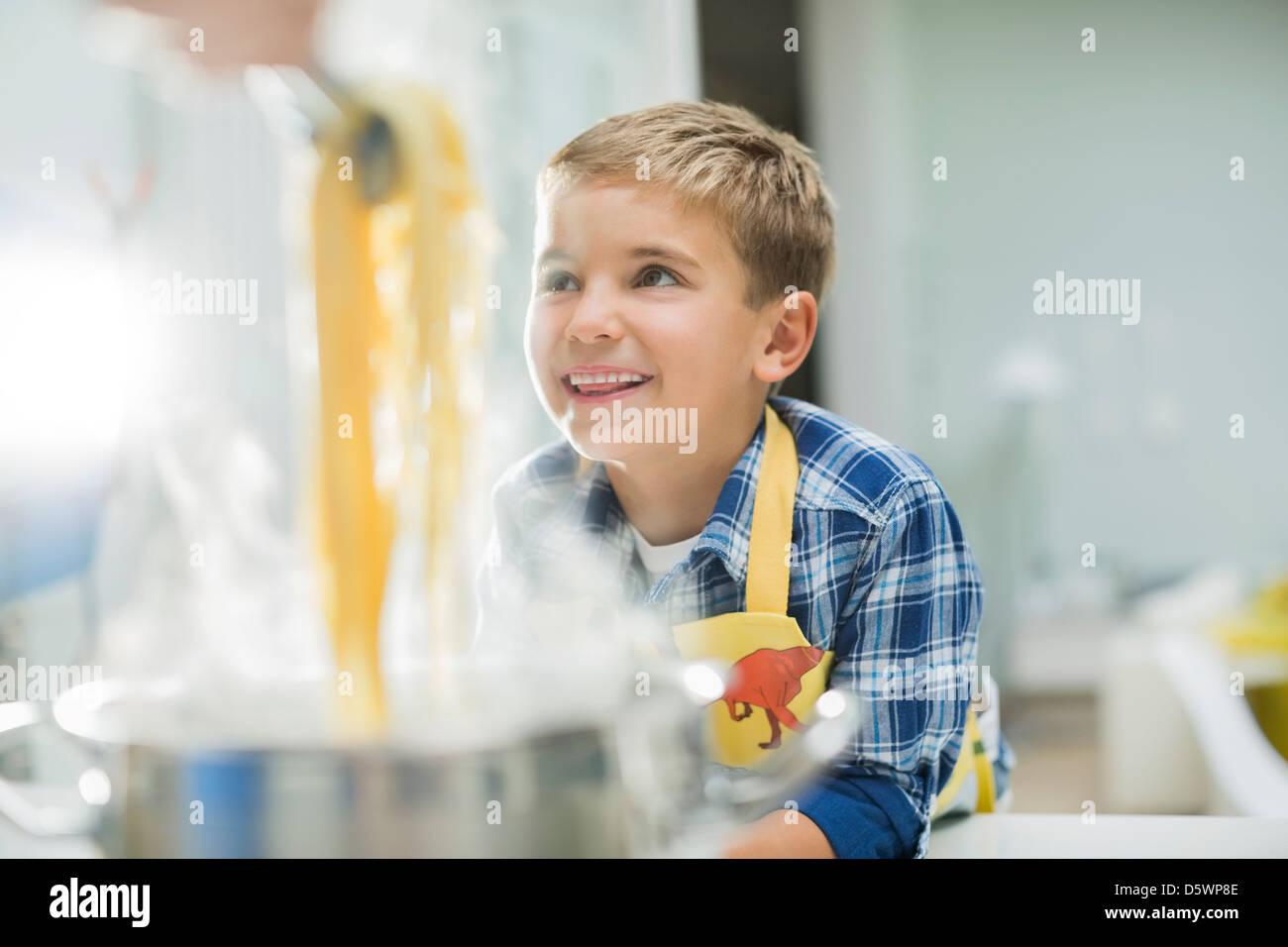 Boy smiling in kitchen Photo Stock