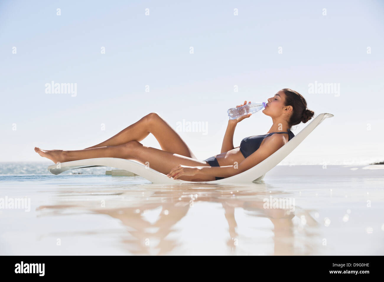 Belle femme l'eau potable sur la plage Photo Stock