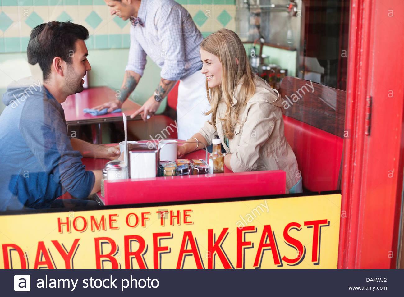 Voir à travers la vitre du couple having coffee at diner Photo Stock