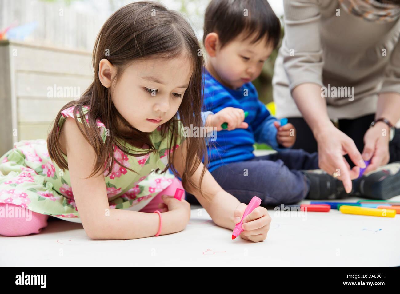 La mère et deux enfants dessin dans jardin Photo Stock