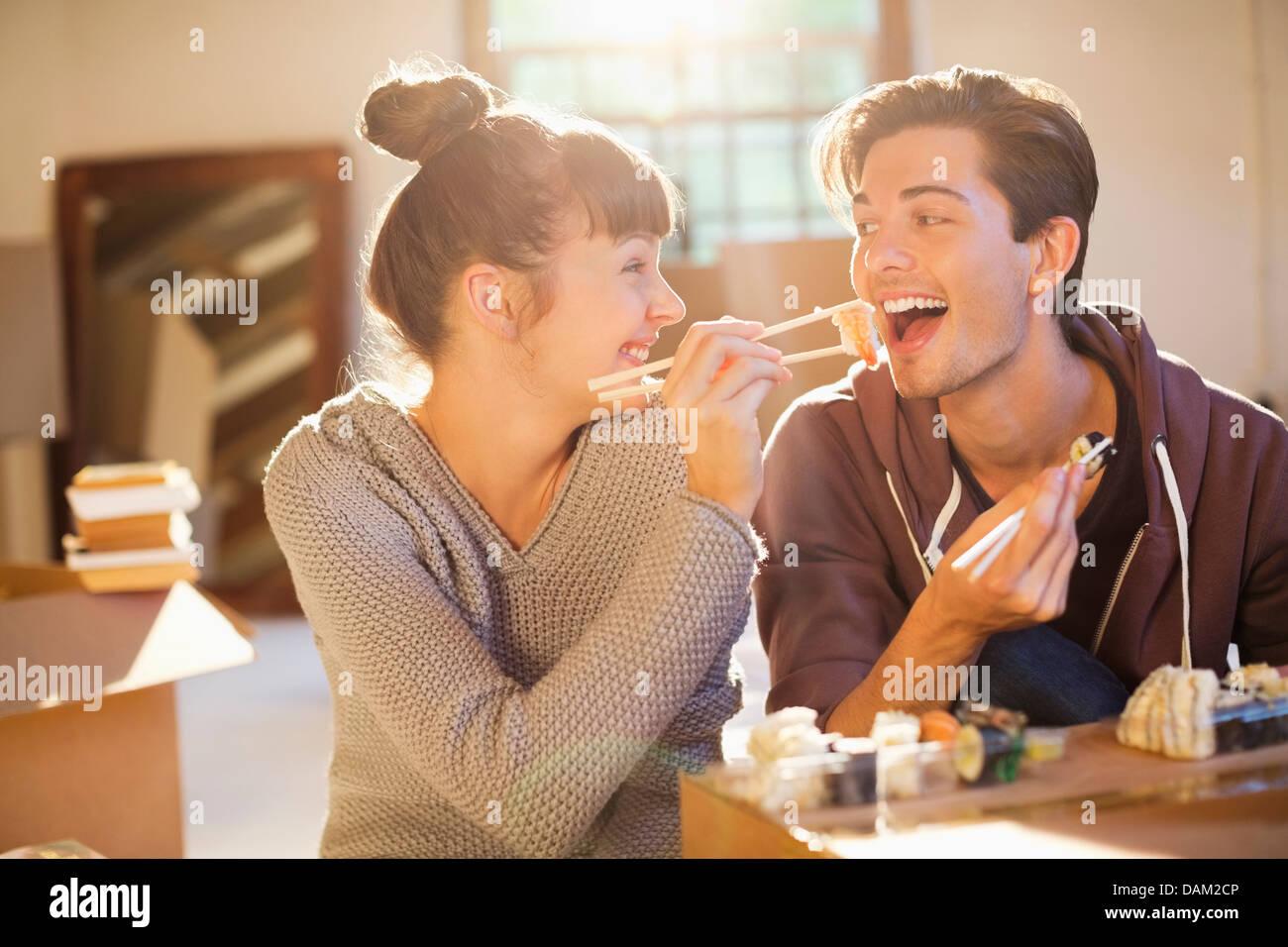 Couple eating sushi ensemble à new home Photo Stock