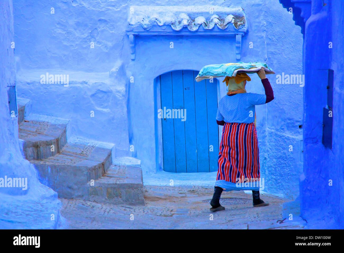Femme en costume traditionnel portant un plateau de pâte à pain, Chefchaouen, Maroc, Afrique du Nord Photo Stock