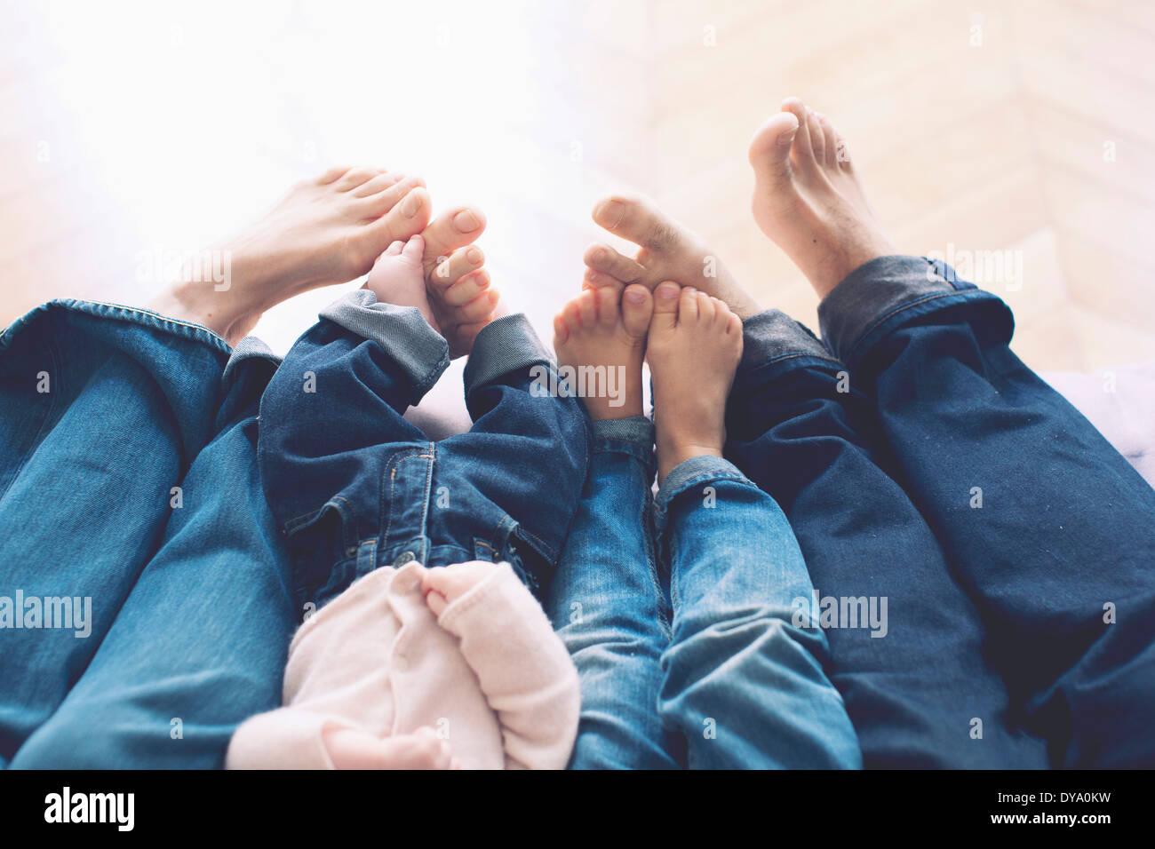 Jambes étendues et pieds nus de famille avec deux enfants Photo Stock