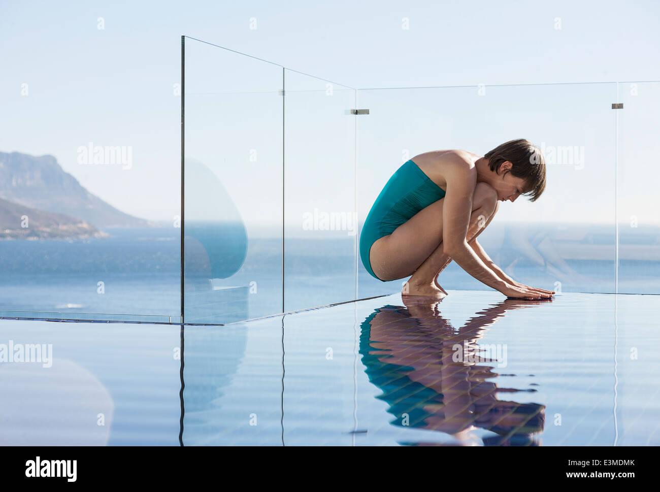 Femme accroupie au-dessus d'une piscine à débordement avec vue sur l'océan Photo Stock