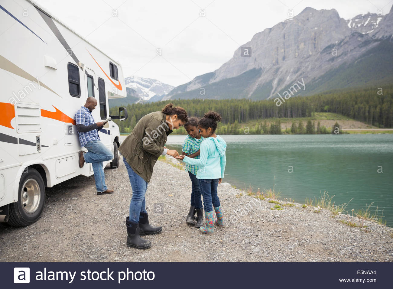 Family standing at lakeside près de RV Photo Stock