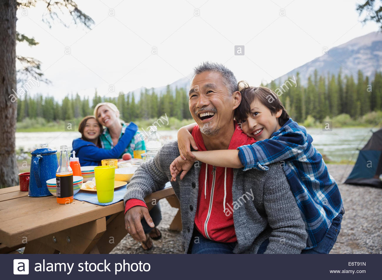 Family relaxing together at campsite Photo Stock