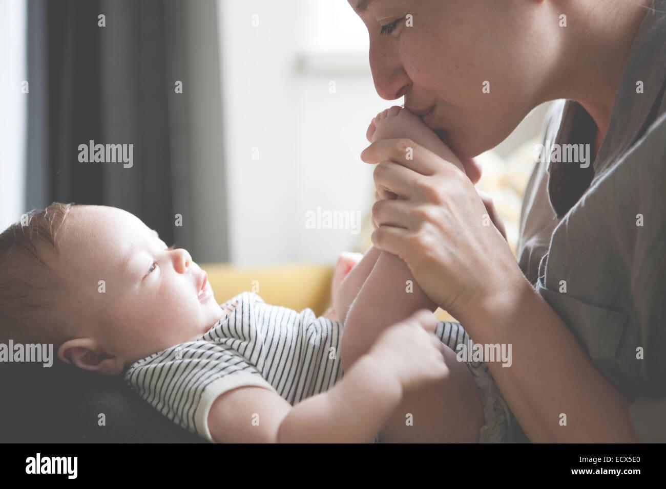 Mother holding et d'embrasser les pieds du bébé peu Photo Stock