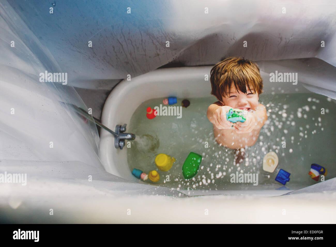 Boy (2-3) en jouant avec des jouets dans la baignoire Photo Stock