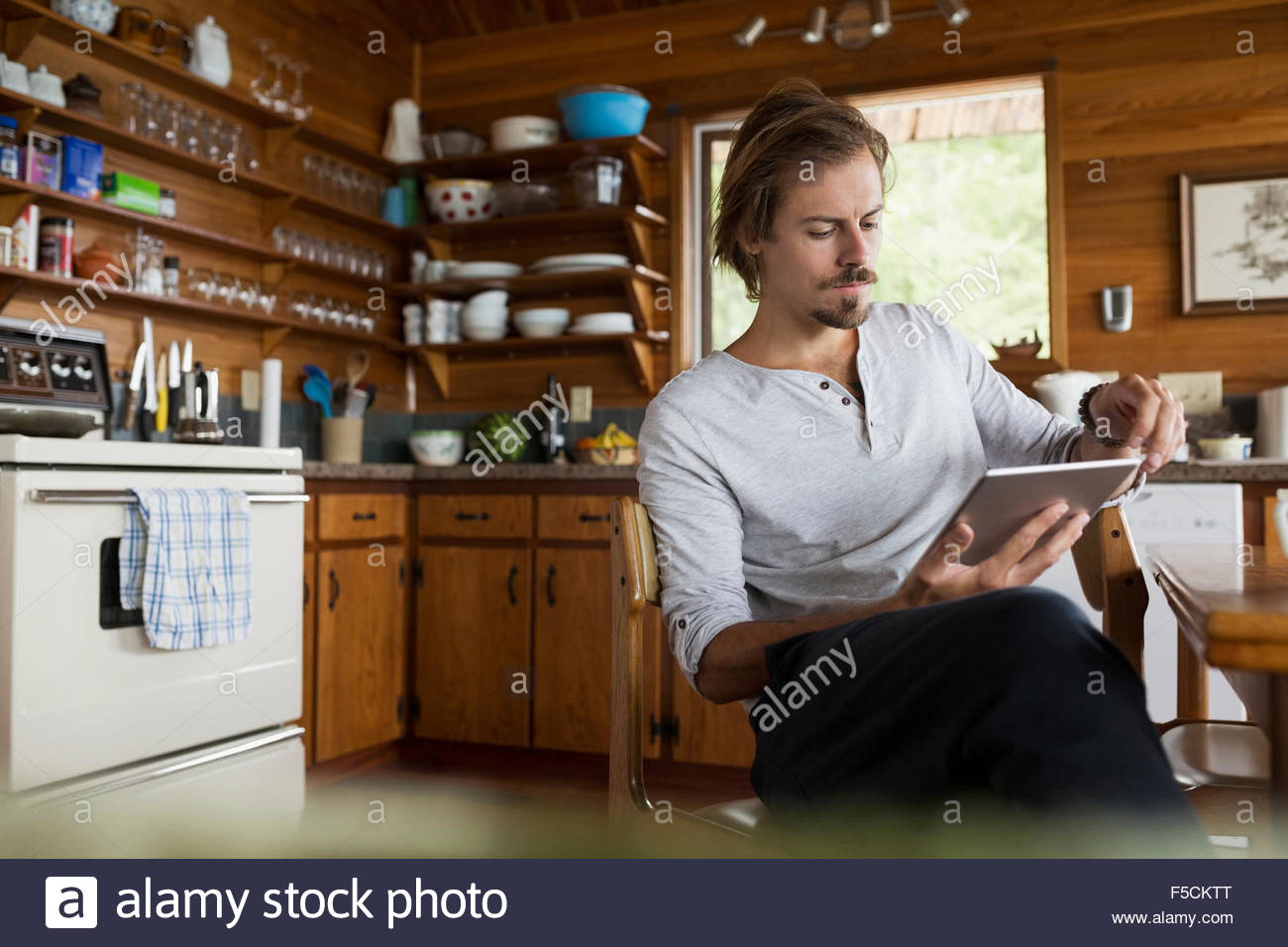 Man using digital tablet de cabin table de cuisine Photo Stock