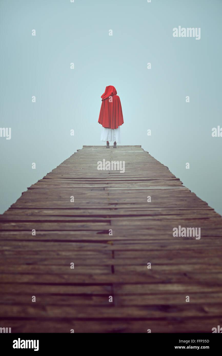 Femme seule habillée d'une robe à capuchon rouge dans un misty pier Photo Stock