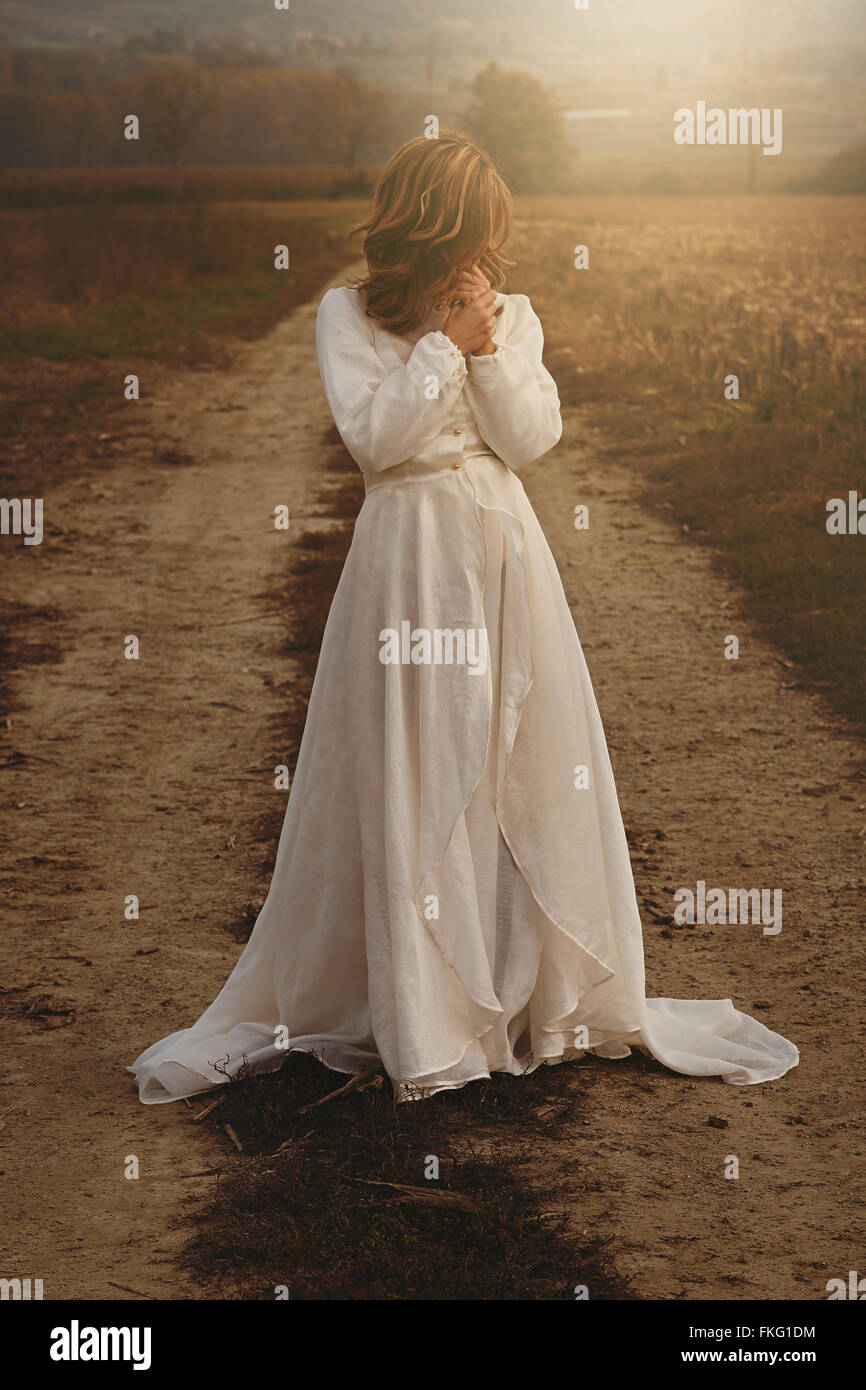 Femme seule avec bride dress vintage dans la campagne . Pureté et d'innocence Photo Stock