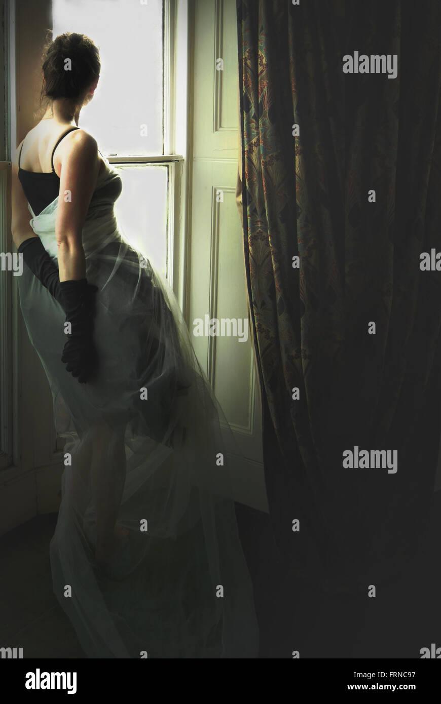 Jeune femme élégante debout près de la fenêtre dans vieille maison Photo Stock
