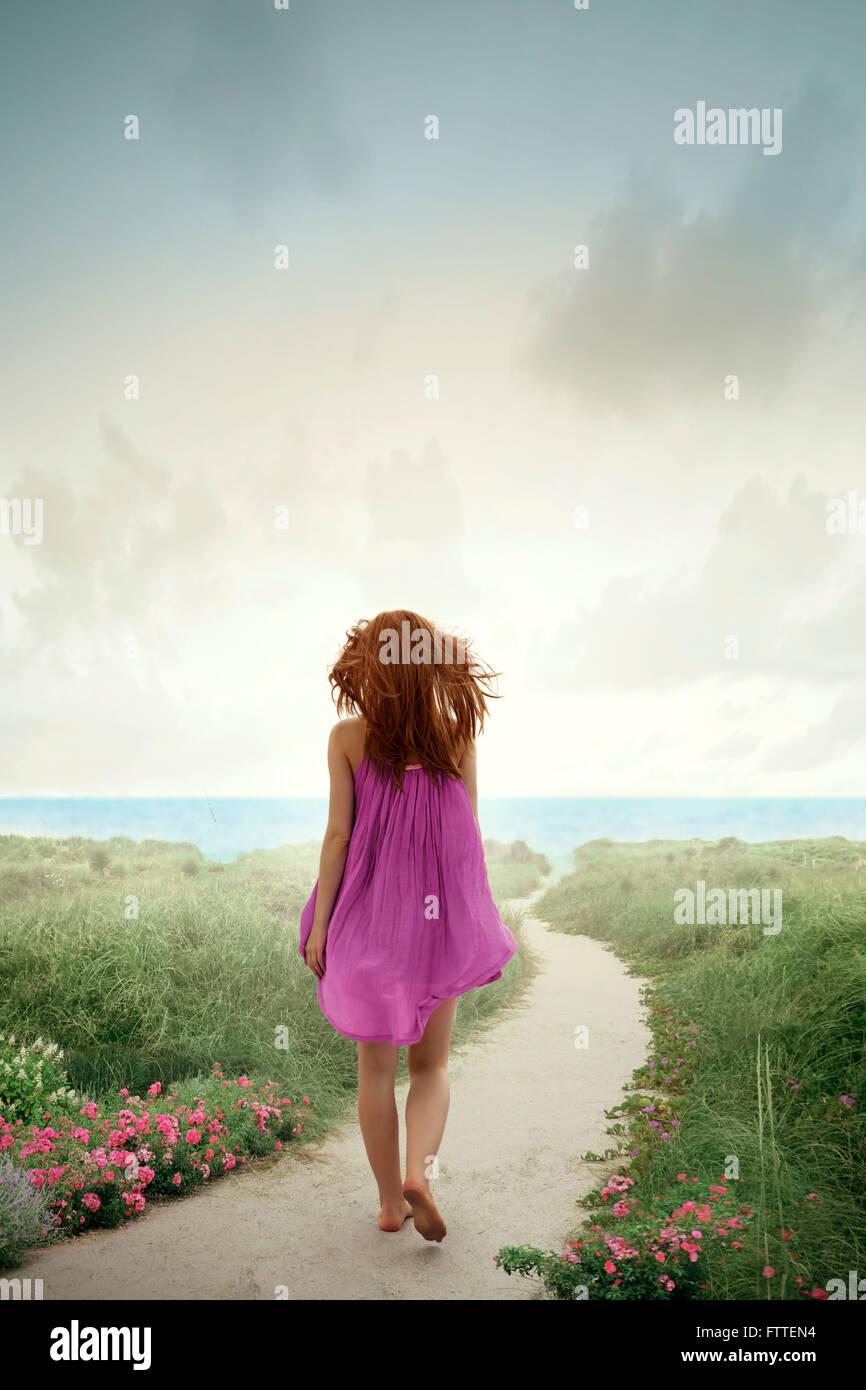 Femme marche sur la plage fleurie Photo Stock