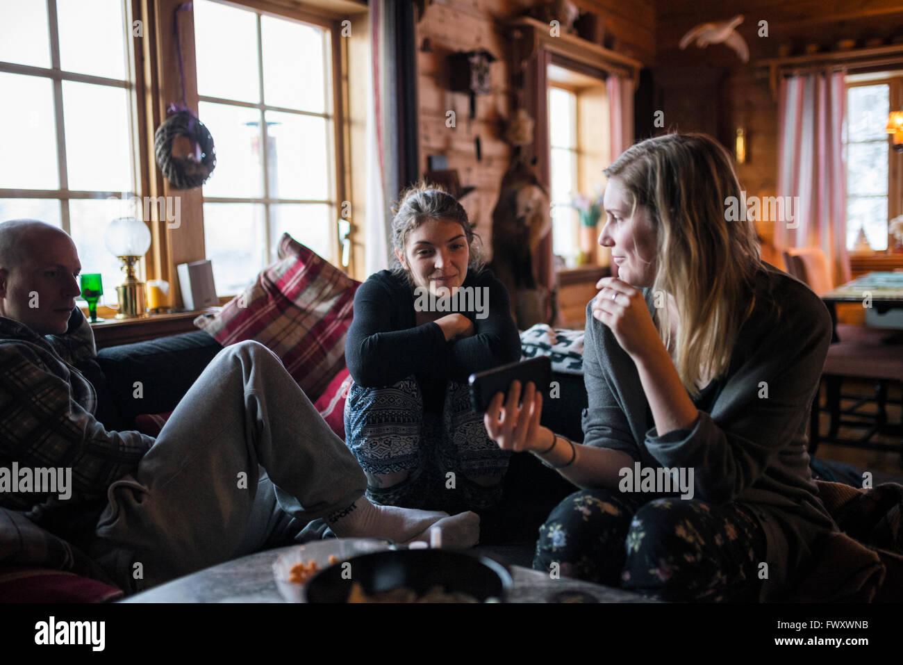 La Suède, jeune femme montrant smart phone à des amis en log cabin Banque D'Images