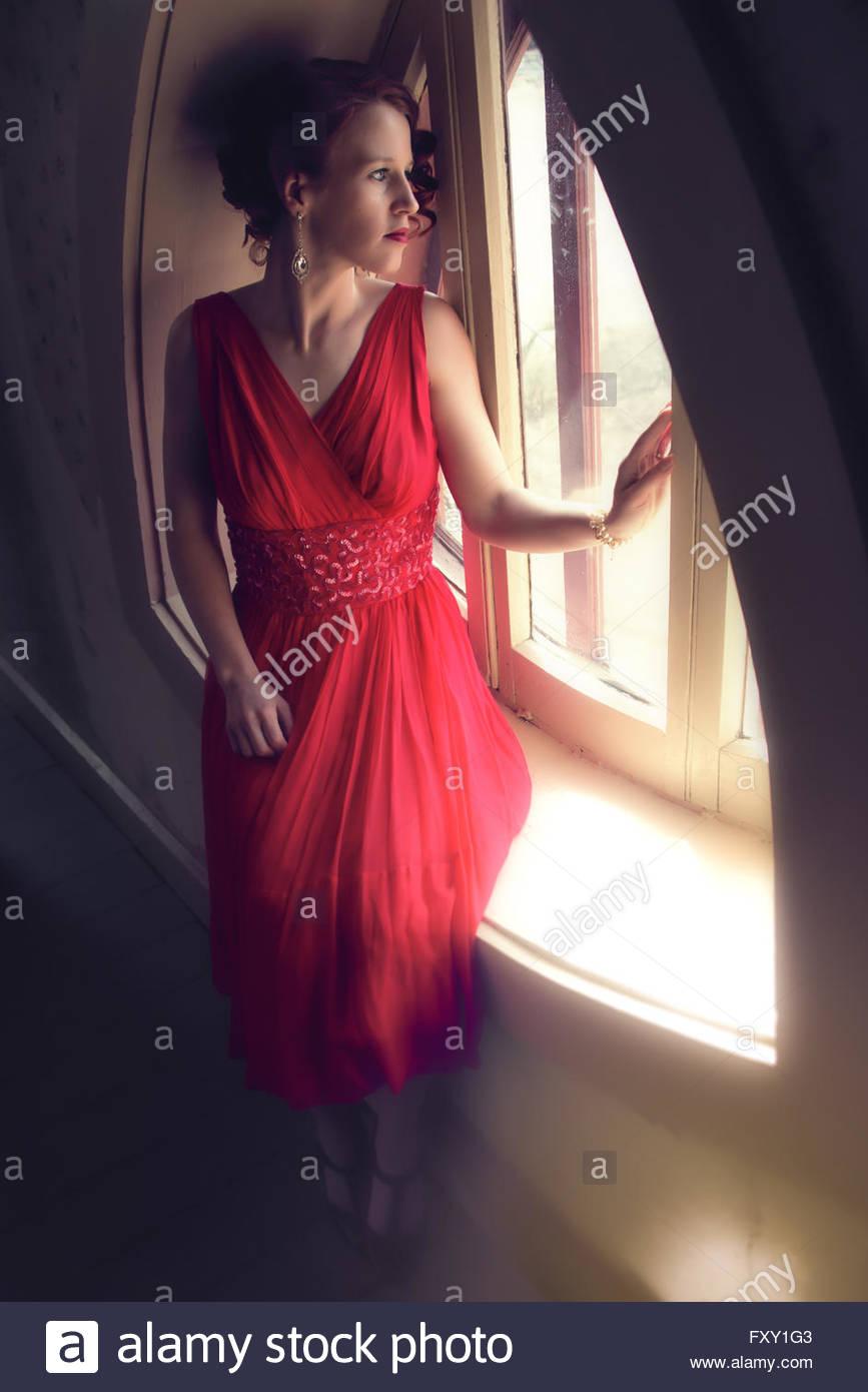 Femme en robe de soirée des années 40, assis par fenêtre Photo Stock