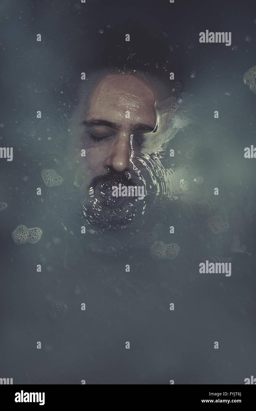 Le concept, l'homme immergé dans l'eau bleue Photo Stock