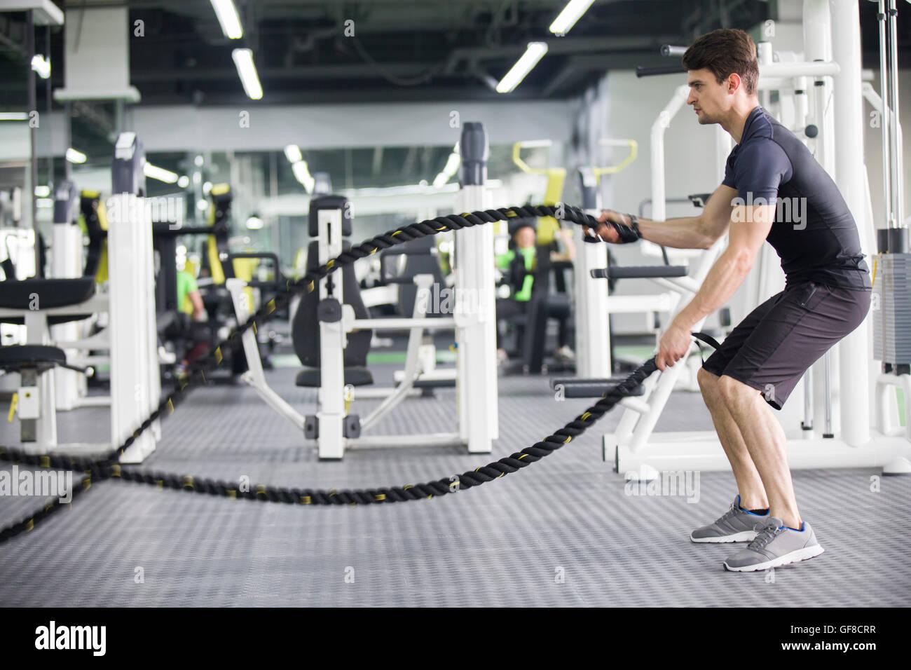 Jeune homme luttant avec l'exercice de corde au gymnase Photo Stock