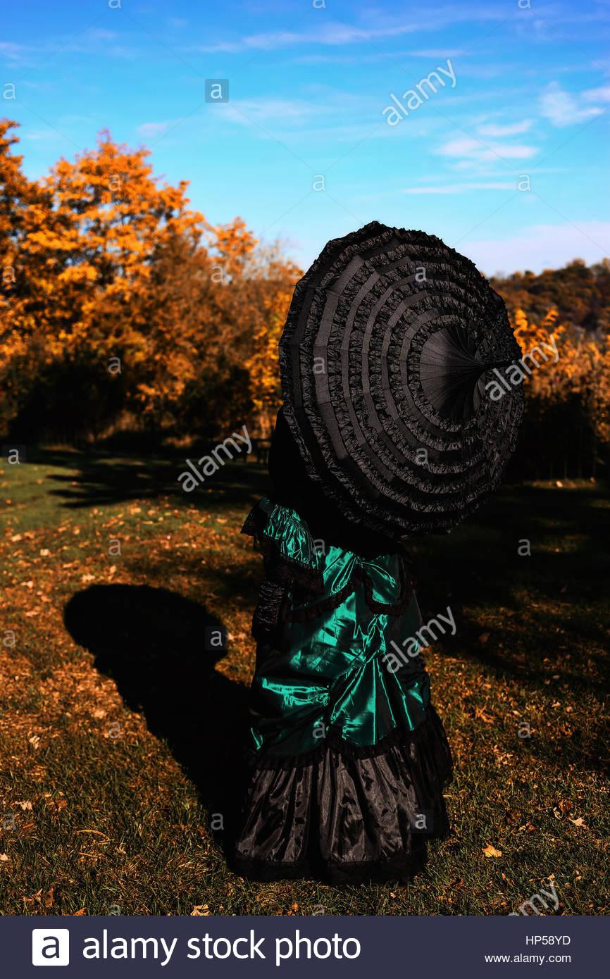 Vue arrière du Victorian woman holding an umbrella Photo Stock