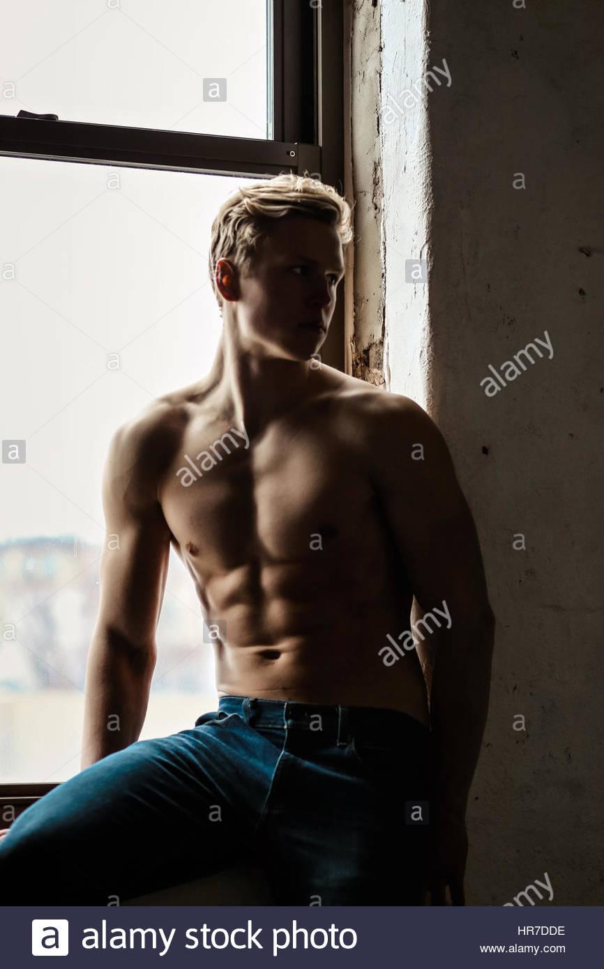 Jeune homme torse nu près d'une fenêtre Photo Stock