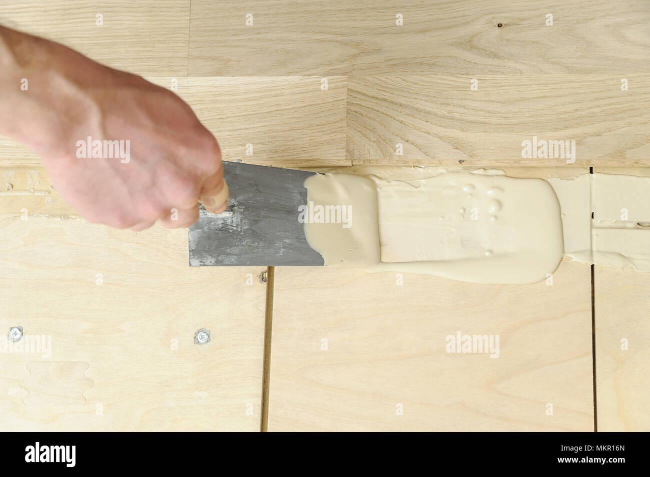 scieries de pose de parquet worker met la colle sur le sol banque d 39 images photo stock. Black Bedroom Furniture Sets. Home Design Ideas
