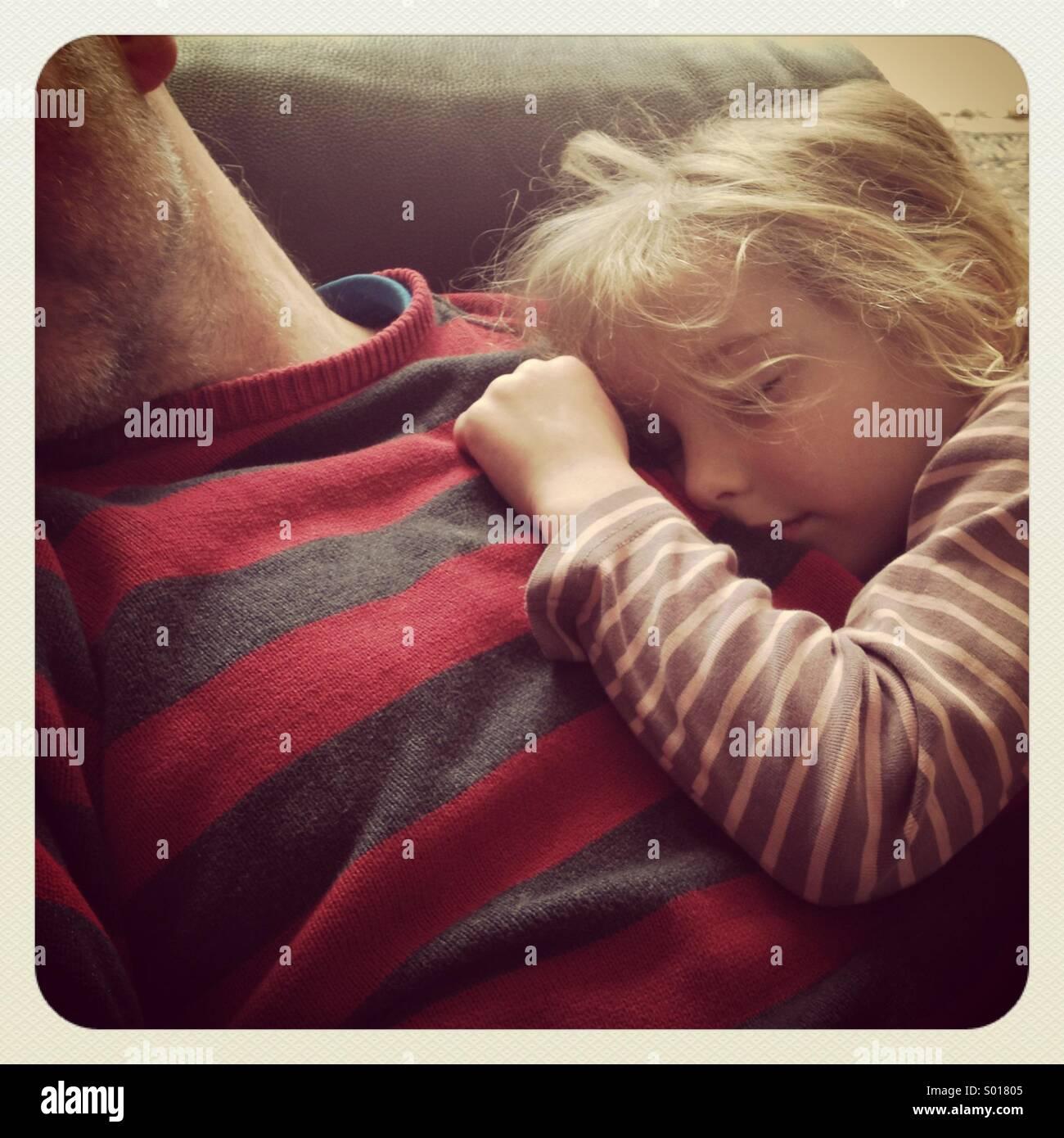 Une fille endormie sur la poitrine de son père Photo Stock