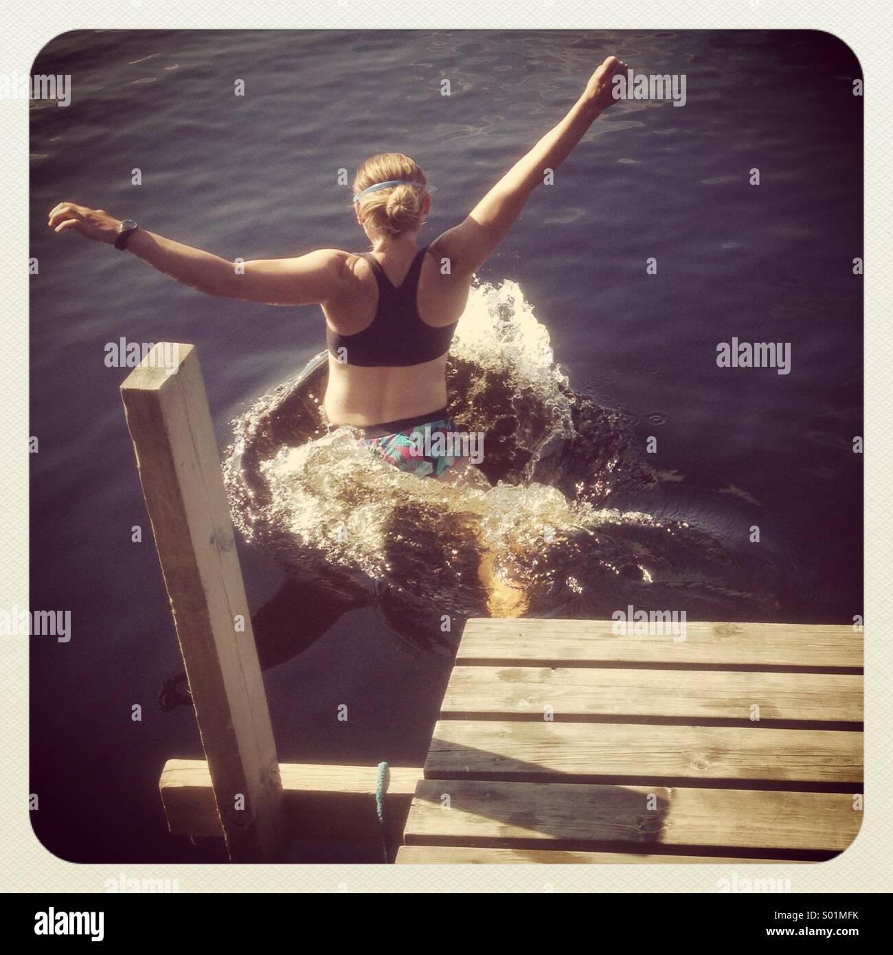 Une femme sautant hors d'une jetée dans un lac Photo Stock