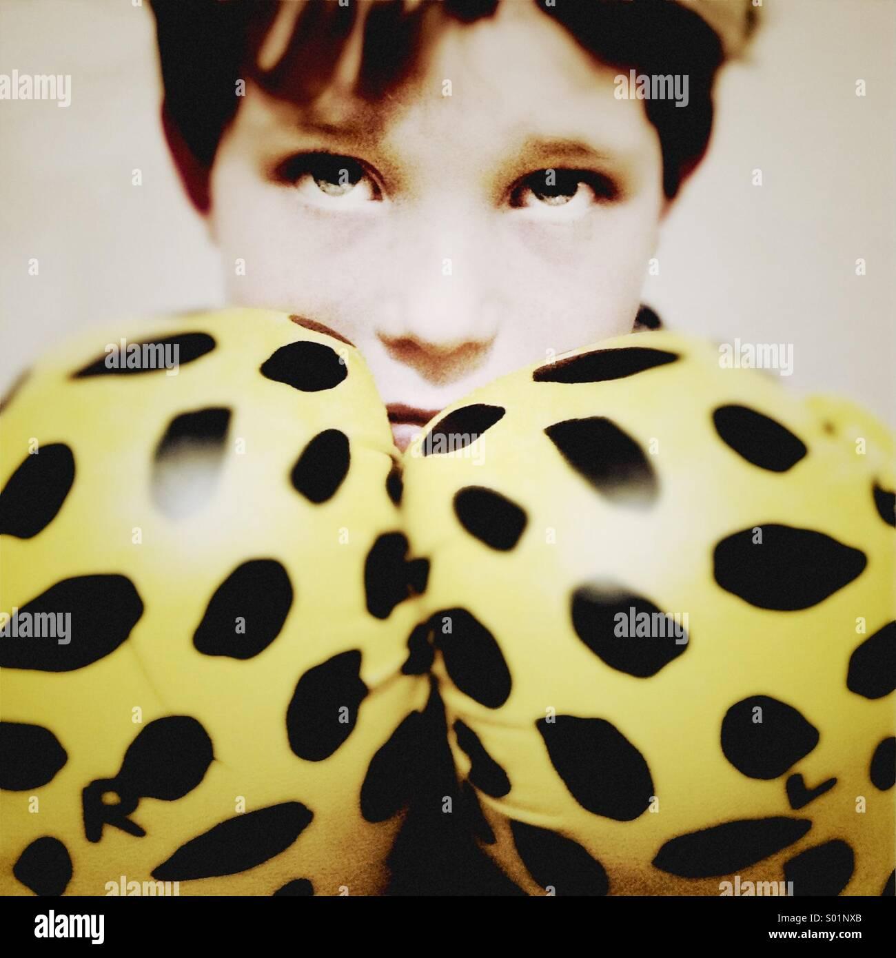 Jeune garçon portant des gants de boxe a l'air de grands yeux sur une posture défensive Photo Stock