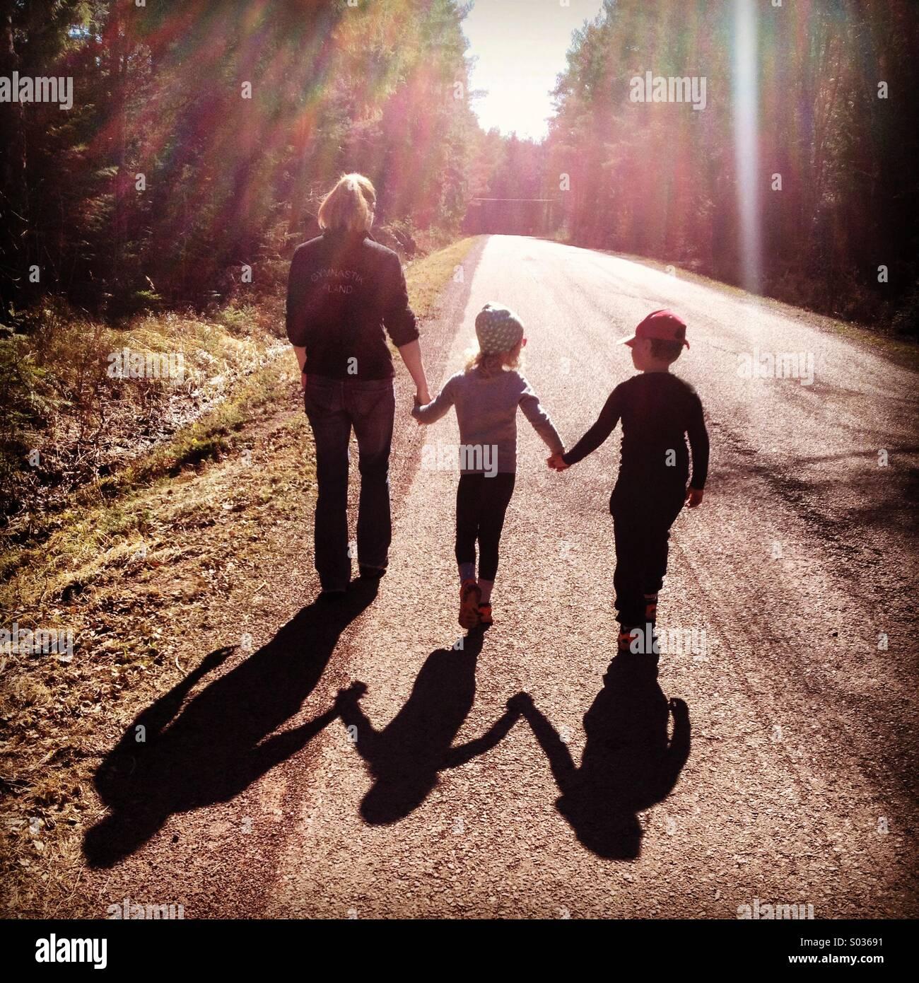Une mère marche main dans la main avec ses enfants dans le soleil du printemps... Photo Stock