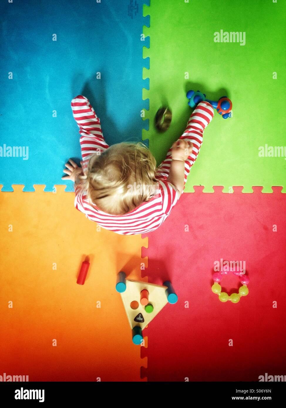 Bébé jouant sur le tapis de jeu colorées Photo Stock
