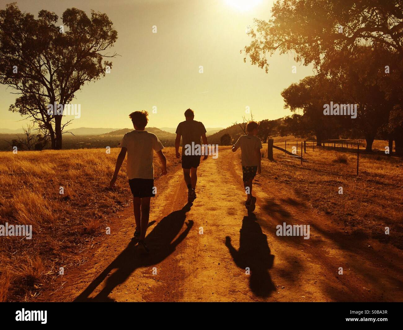 Un père et ses deux fils se réveiller dans le coucher du soleil en pays Australie Photo Stock