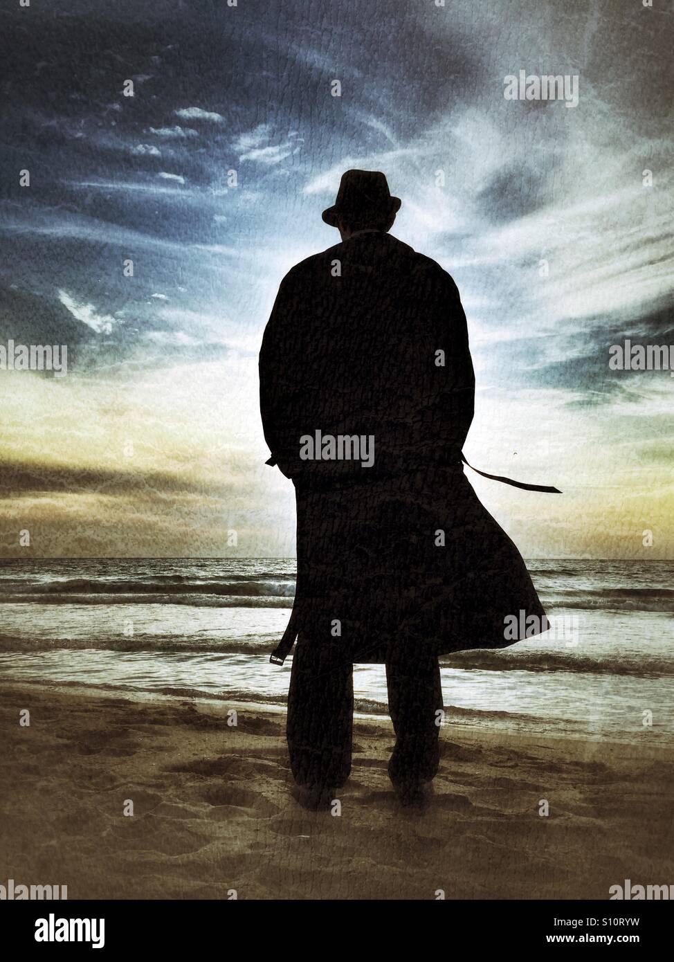 Homme dans un manteau de la mer au coucher du soleil Photo Stock