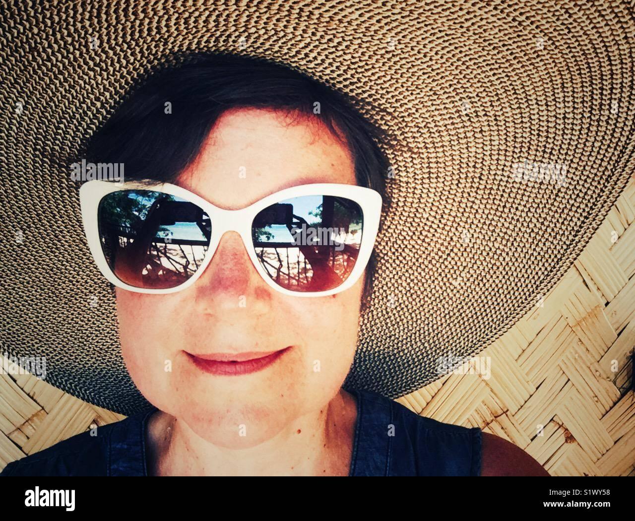 Happy smiling woman in grand chapeau et 50-s lunettes cerclées de blanc de style Photo Stock