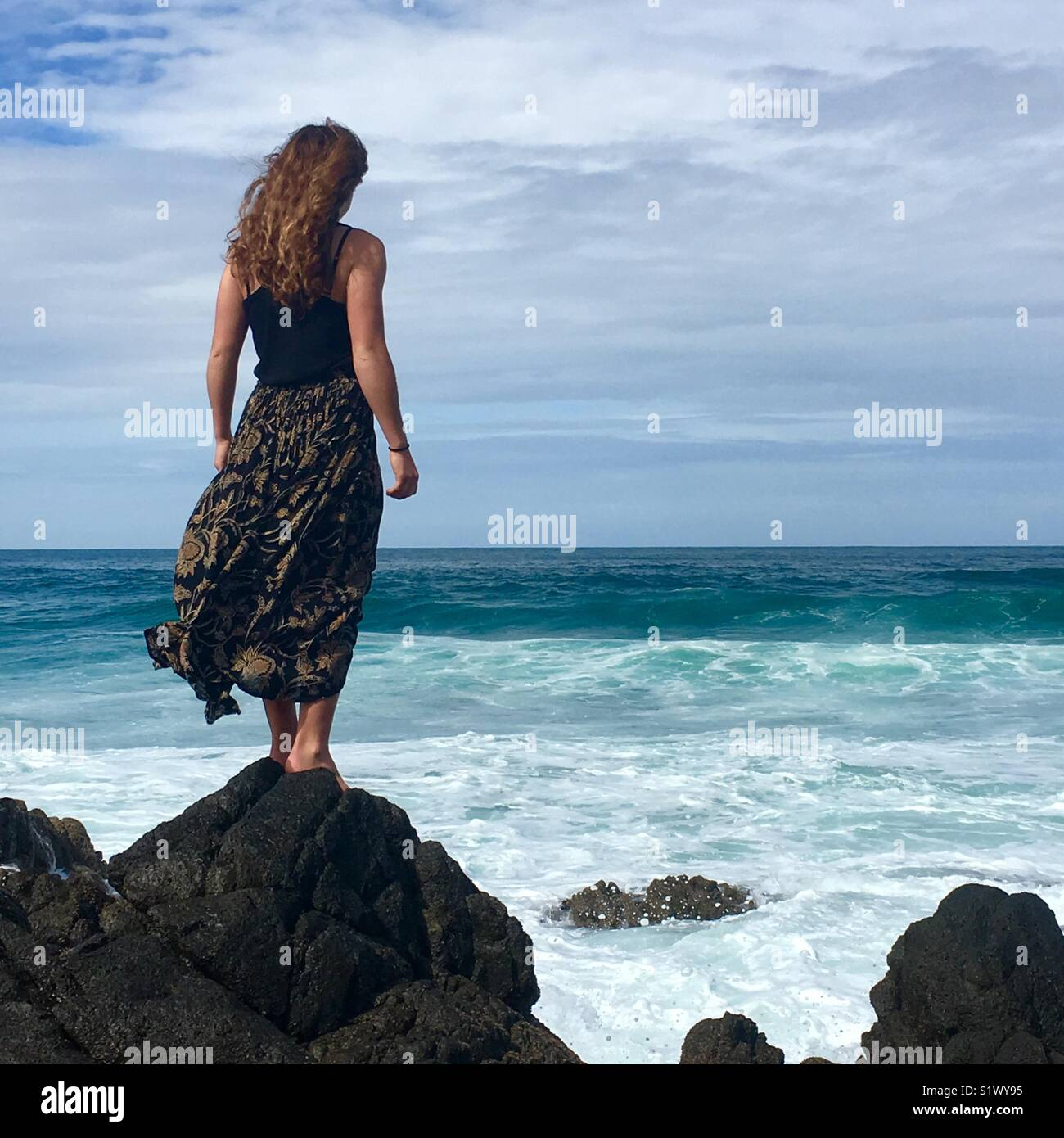 Jeune fille se tient sur des rochers surplombant la mer Photo Stock