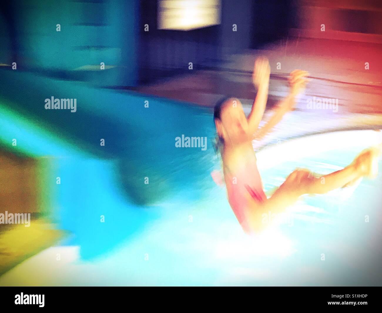 Une fille tire hors d'un toboggan et d'écumage plus d'une piscine. Photo Stock