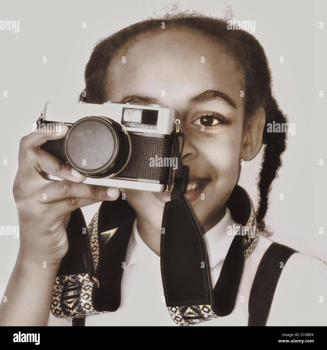 Une jeune fille tenant une caméra vintage de son œil. Photo Stock