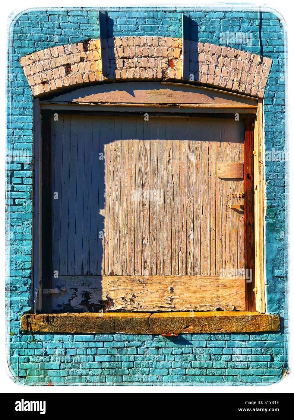 Mur de brique turquoise avec la porte en bois en difficulté Photo Stock