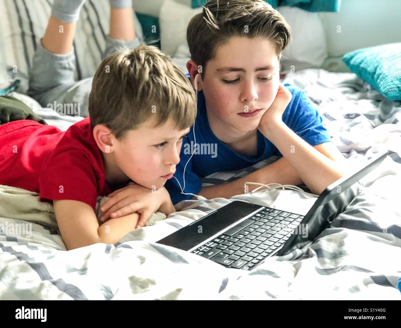 Deux jeunes garçons regarder YouTube sur un dimanche après-midi de détente au Royaume-Uni. Photo Stock