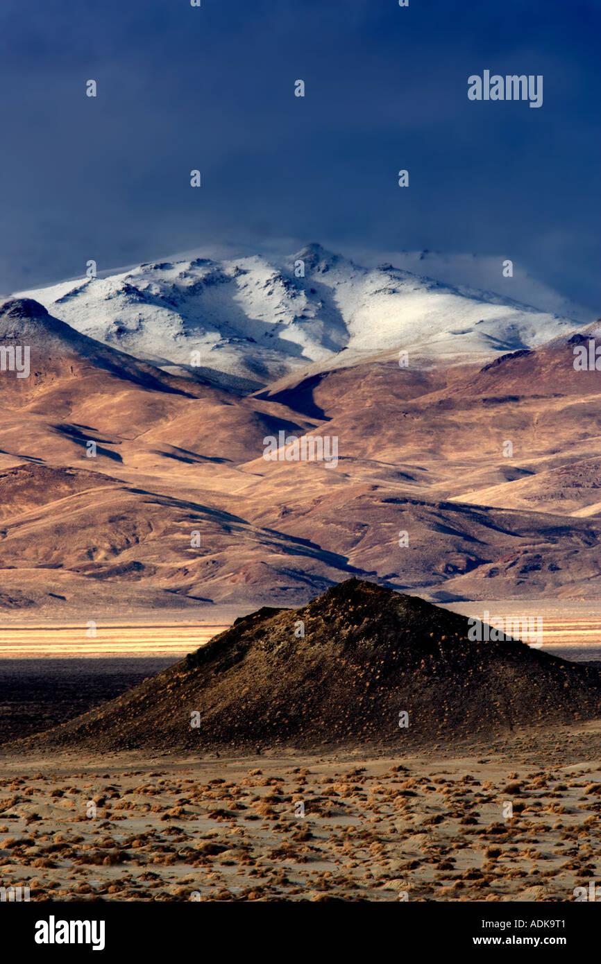 Piccolo cono di scorie e montagne coperte di neve Black Rock Desert National Conservation Area Nevada Immagini Stock