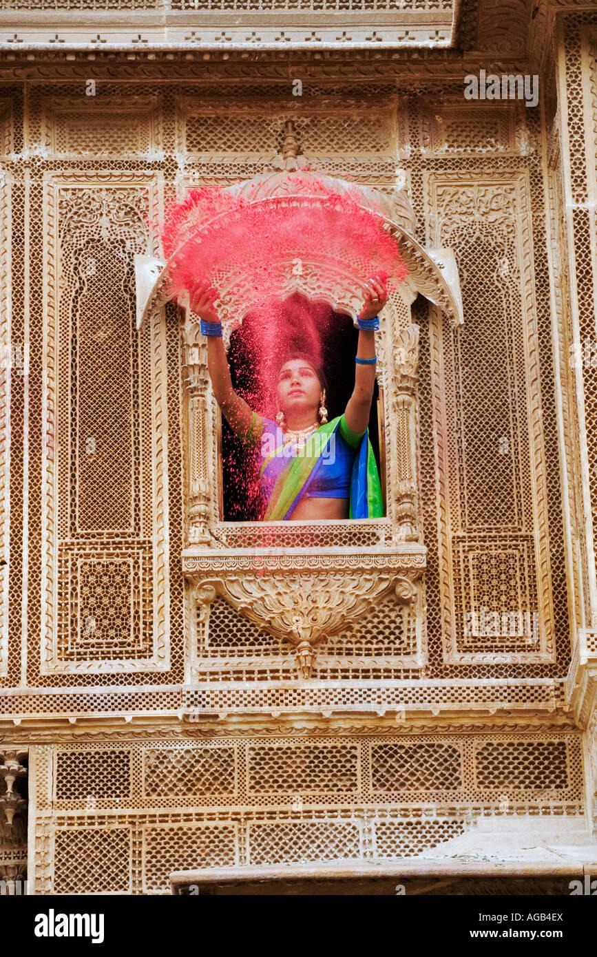 Donna gettando vivacemente colorato holi polvere attraverso una finestra di un haveli Immagini Stock
