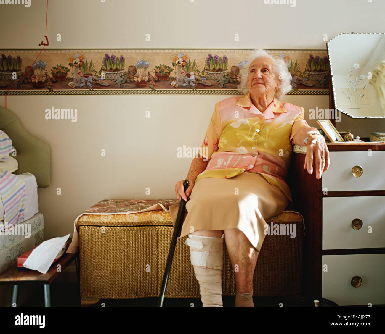 Donna anziana nella sua camera da letto Immagini Stock