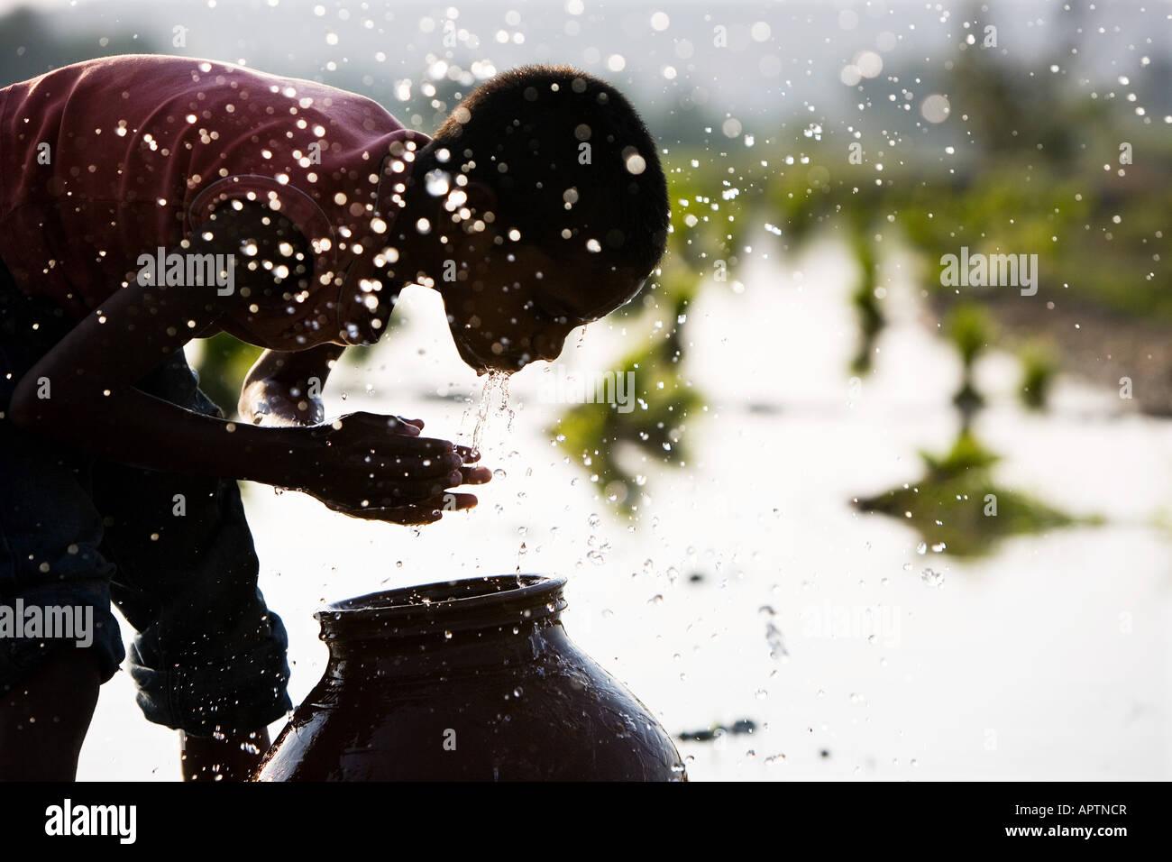 Silhouette di un rurale villaggio indiano boy volto di lavaggio da una pentola di creta accanto a un risone campo. Immagini Stock