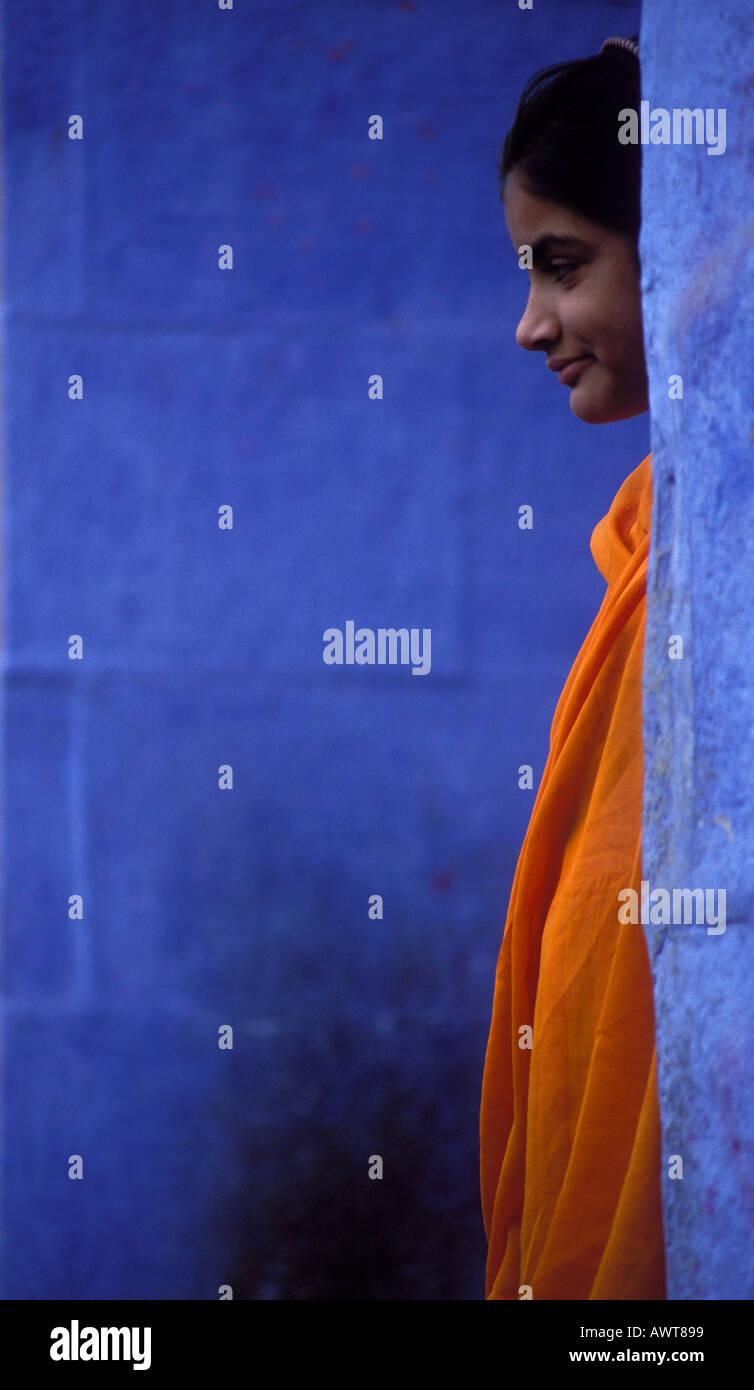 Giovani donne che indossano orange Sari si erge tra pareti blu Jodhpur Rajasthan in India Immagini Stock