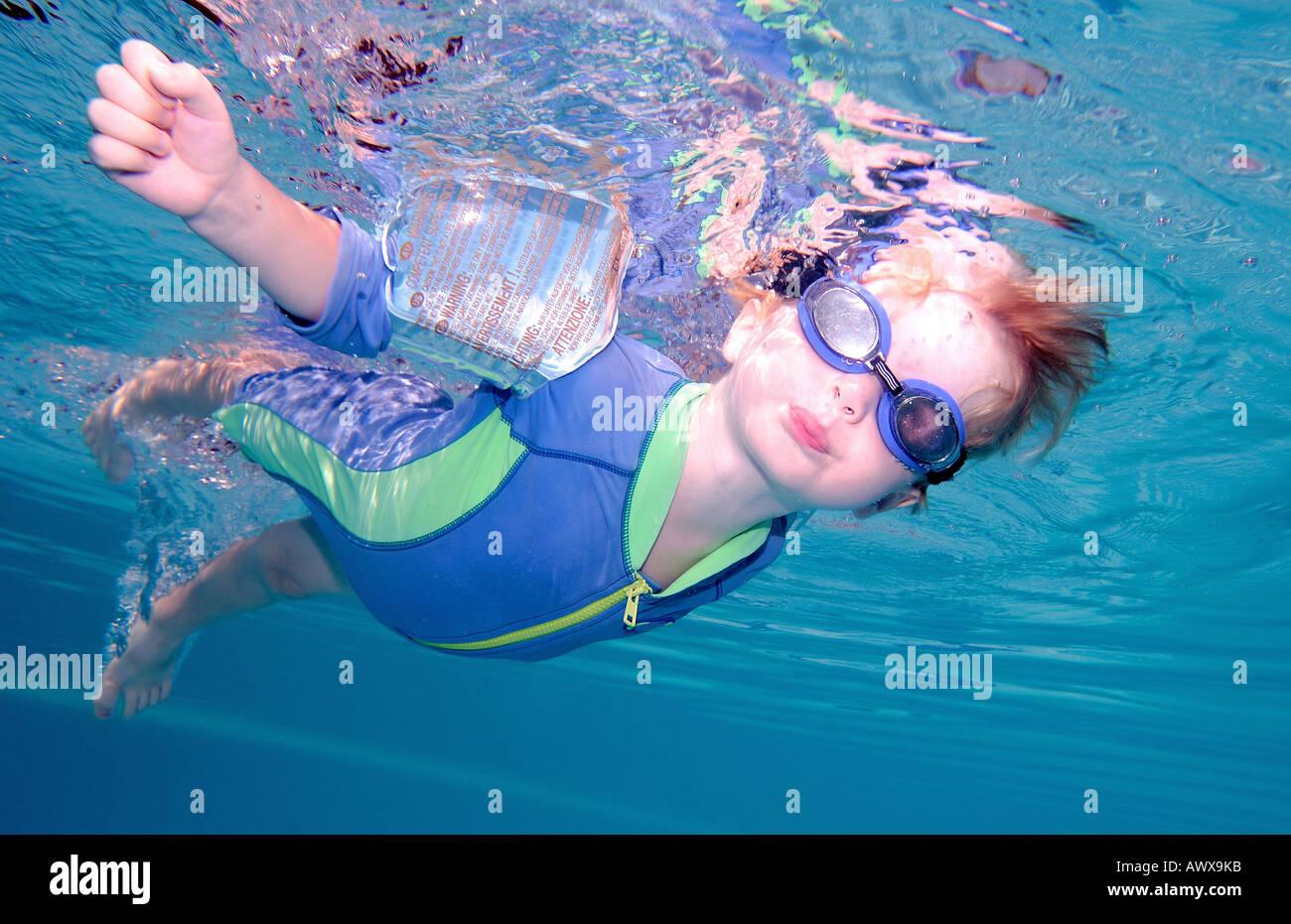 Ragazzo o bambino nuoto sott'acqua e apnea con occhiali di sicurezza su Immagini Stock