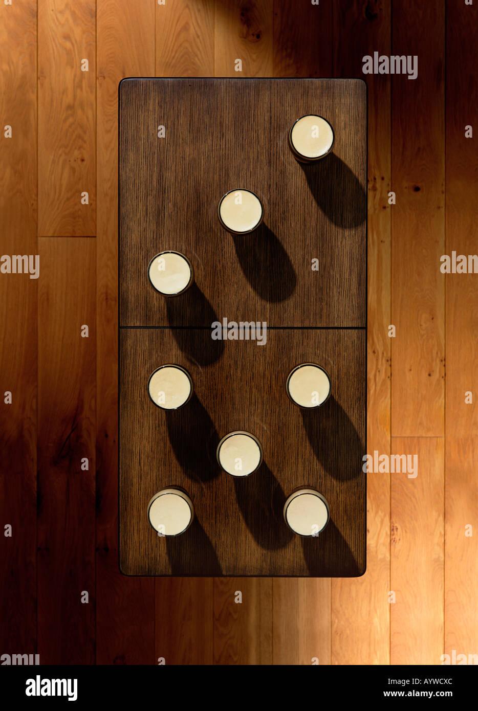Un overhead shot di una tabella con alcune pinte di posto su di esso anche per apparire come un domino Immagini Stock